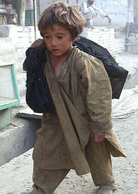 "A young Afghan boy walks near the Pakistan-Afghan border area at Torkham, some 180 km northwest of Islamabad, scavenging for food and items of value September 15, 2001. Pakistan said on Saturday it would comply with all U.N. resolutions that seek to combat ""international terrorism"", but its military was unlikely to take part in operations beyond its border. REUTERS/Aziz Haidari"